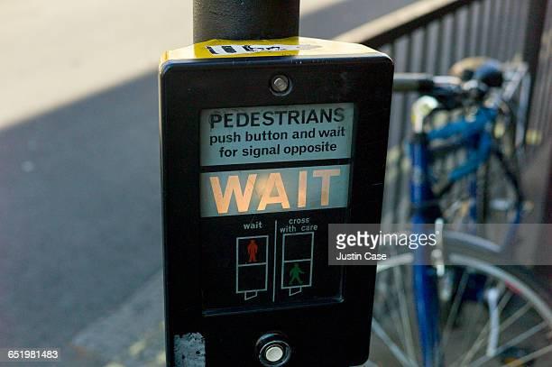 Pedestrians wait sign at traffic light