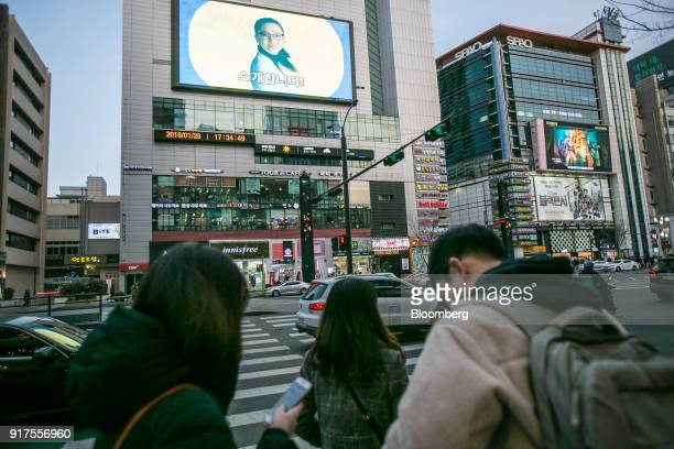 Pedestrians wait to cross a road as electronic screens display advertisements in Seoul South Korea on Sunday Jan 28 2018 5G the fifthgeneration...