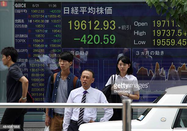 Pedestrians wait to cross a road in front an electronic board displaying the the Nikkei 225 Stock Average figure outside a securities firm in Tokyo...