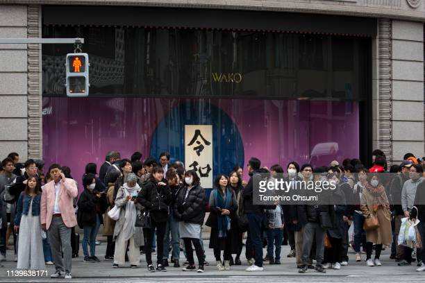 Pedestrians wait to cross a road in front of a calligraphy work showing the name of Japan's next imperial era 'Reiwa' displayed in the Ginza district...