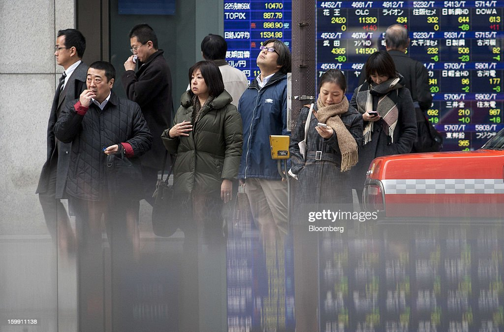 Pedestrians wait to cross a road in front of an electronic stock board outside a securities firm in Tokyo, Japan, on Wednesday, Jan. 23, 2013. Japan shares declined, with the Nikkei 225 Stock Average posting its first three-day decline since elections were called, as the yen climbed after the Bank of Japan said it will wait a year to add open-ended stimulus. Photographer: Tomohiro Ohsumi/Bloomberg via Getty Images