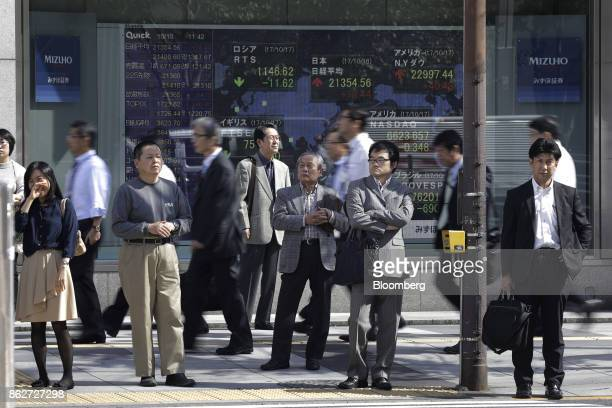 Pedestrians wait to cross a road in front of an electronic stock board outside a securities firm in Tokyo Japan on Wednesday Oct 18 2017 As Prime...
