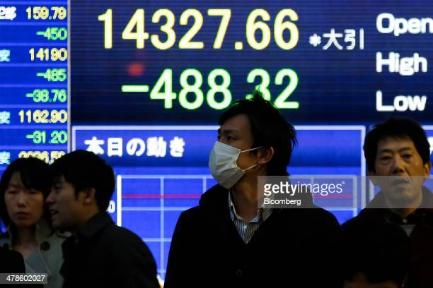 Pedestrians wait to cross a road in front of an electronic stock board displaying the closing figure of the Nikkei 225 Stock Average outside a...