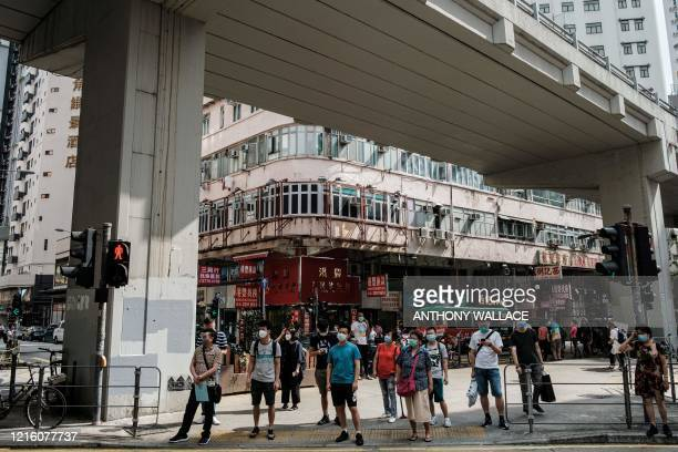 Pedestrians wait to cross a road in Hong Kong on May 29 2020 China faced growing international pressure May 29 over its move to impose a security law...