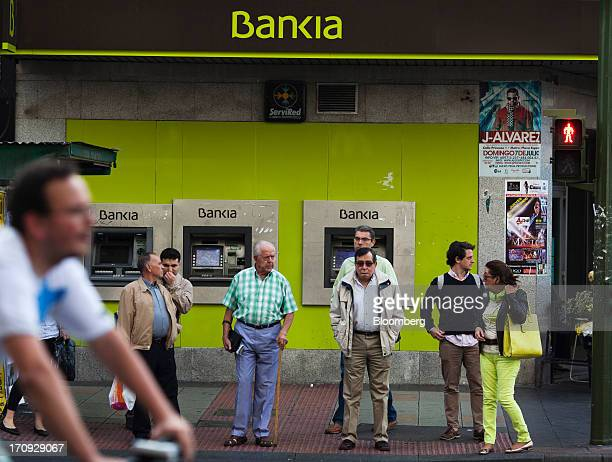 Pedestrians wait to cross a road outside a branch of Bankia SA in Madrid Spain on Thursday June 20 2013 Bailing out Bankia SA Spain's fourthbiggest...