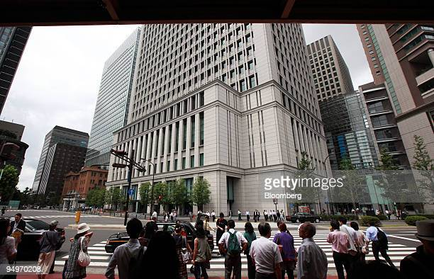 Pedestrians wait to cross an intersection in front of the building which houses the Hitachi Ltd. Headquarters, center, in Tokyo, Japan, on Monday,...