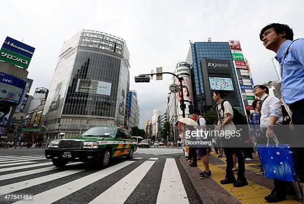 Pedestrians wait to cross an intersection in the Shibuya district of Tokyo Japan on Wednesday June 17 2015 Bank of Japan Governor Haruhiko Kuroda...
