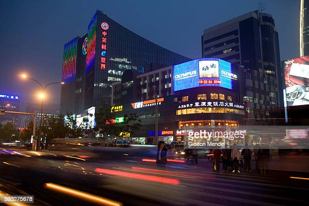 Pedestrians wait to cross at an intersection during the evening rush hour in the busy Zhongguancun district which is known as the computer district...