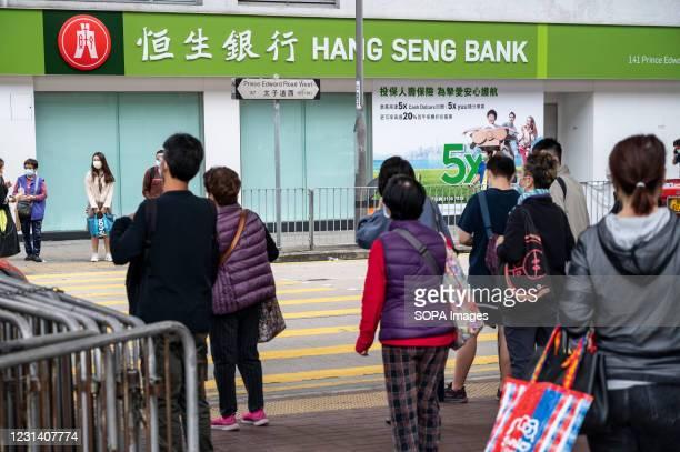 Pedestrians wait to cross the street in front of a Hang Seng Bank branch in Hong Kong.