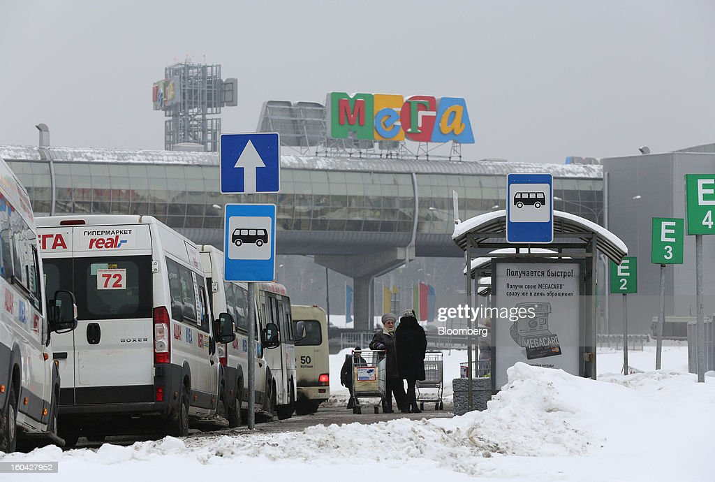 Pedestrians wait with their shopping carts at a bus stop outside the MEGA Belaya Dacha shopping complex, constructed by the real estate development arm of Inter Ikea Systems BV and one of Europe's largest malls, in Moscow, Russia, on Thursday, Jan. 31, 2013. Russian shopping-mall construction may climb to a record this year as retailers take advantage of rising sales by moving into bigger, more modern buildings, Cushman & Wakefield Inc. said. Photographer: Andrey Rudakov/Bloomberg via Getty Images