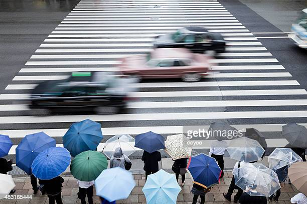 Pedestrians waiting to cross a busy road on a rainy day
