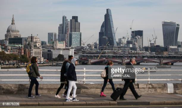 Pedestrians waling through Waterloo Bridge with the skyline of the City of London in the background on October 27 2016 Britain's economy won a double...