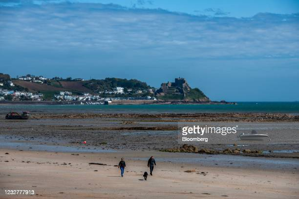Pedestrians walk a dog along a beach in view of Mont Orgueil Castle in Gorey, Jersey, on Saturday, May 8, 2021. Frances maritime minister suggested...