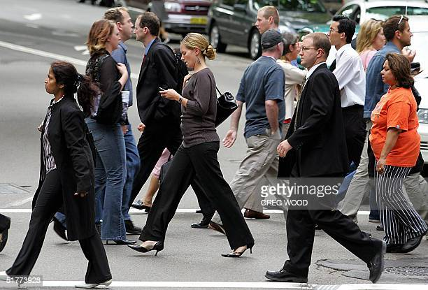Pedestrians walk across a busy Sydney street intersection 22 November 2004 Government figures released 22 November show that Australia is now...