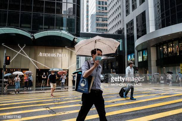Pedestrians walk across a road during heavy rain in Hong Kong on May 29 2020 China faced growing international pressure May 29 over its move to...