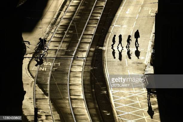 Pedestrians walk across an empty street in Manchester, north west England on January 5 as Britain enters a national lockdown to combat the spread of...