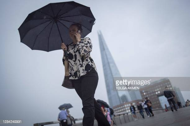 Pedestrians walk across London Bridge in central London on July 27, 2021. - Prime Minister Boris Johnson called for caution Tuesday after Britain...