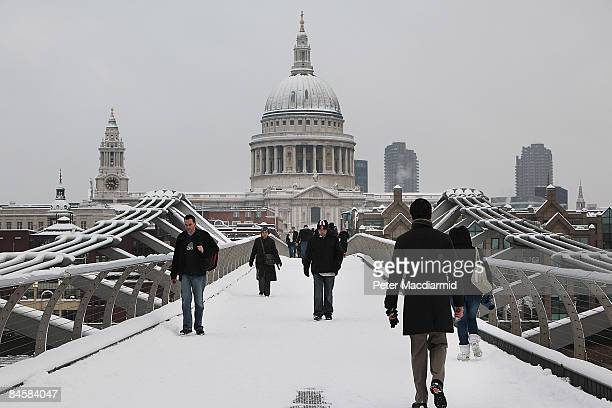 Pedestrians walk across the Millennium Bridge in sight of a snow covered Saint Paul's Cathedral on February 2 2009 in London The United Kingdom has...