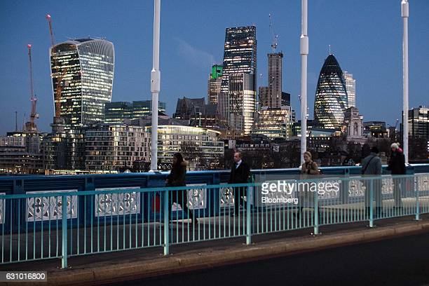 Pedestrians walk across Tower Bridge as skyscrapers including Tower 42 the Heron Tower the Leadenhall building also known as the 'Cheesegrater' 30 St...