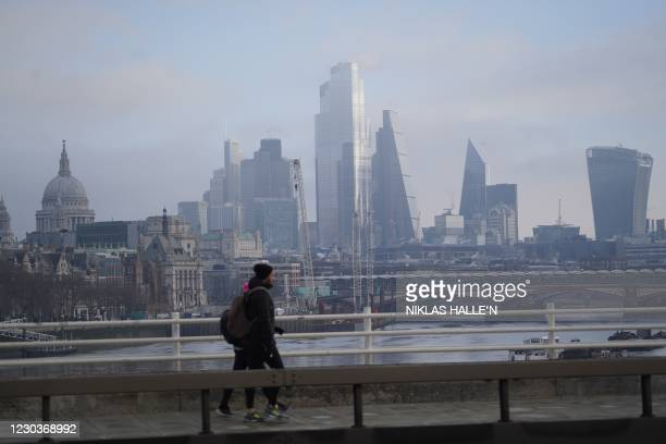 Pedestrians walk along a bridge over the River Thames with skyscrapers and offices of the City of London in the background in London on December 31,...