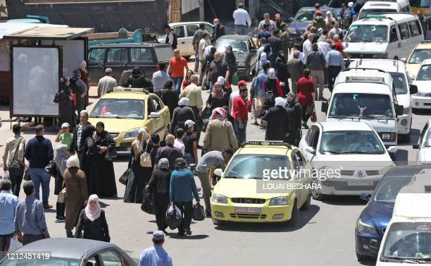 Pedestrians walk along a busy street in the Syrian capital Damascus on May 10, 2020. - Syria's government banned cars with large engines from...