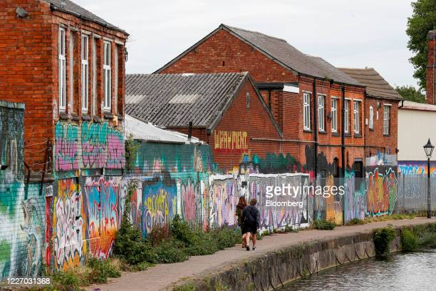 Pedestrians walk along a canal path past former textile businesses painted with street art in Leicester, U.K., on Monday, July 13, 2020. Leicester...