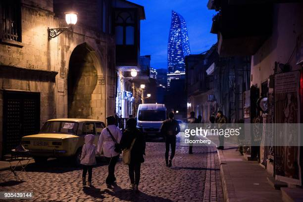 Pedestrians walk along a cobbled street as the Flame Towers stands in the background at night in the Old City of Baku Azerbaijan on Friday March 16...
