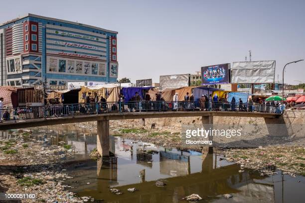 Pedestrians walk along a footbridge over the Kabul River in Kabul Afghanistan on Thursday July 12 2018 US President Donald last year said 16000 US...