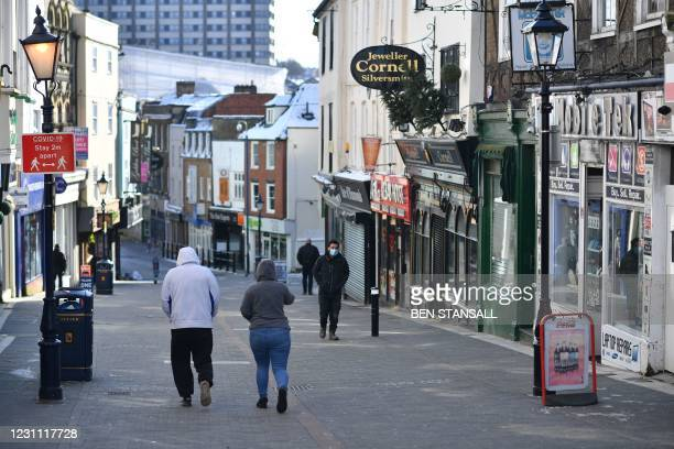 Pedestrians walk along a high street with the shops closed in Maidstone, southeast England, on February 12, 2021 as life continues in Britain's third...