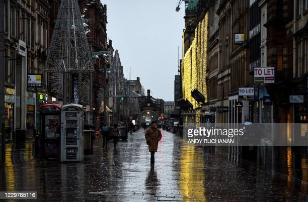 Pedestrians walk along a near-deserted Buchanan Street in central Glasgow, on November 24 during further coronavirus restrictions in the city. -...