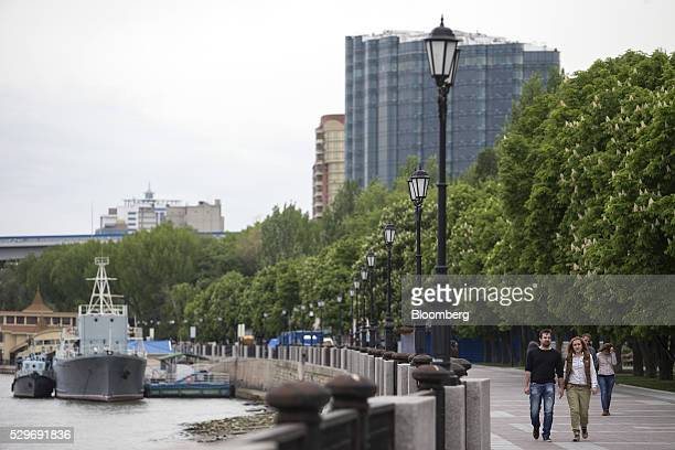 Pedestrians walk along a newly constructed embankment beside the River Don in RostovonDon Russia on Wednesday May 4 2016 The ruble weakened the most...