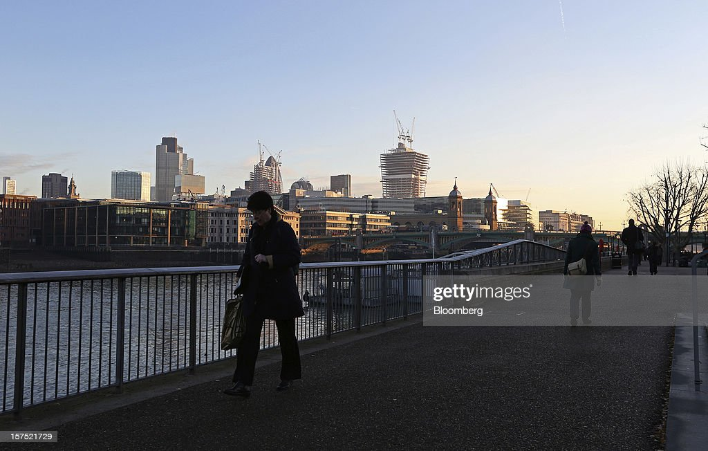 Pedestrians walk along a path on the south side of the River Thames past the financial district, on the north side, in London, U.K., on Friday, Nov. 30, 2012. U.K. banks have become more unwilling to finance development projects without a tenant committed to lease space or a buyer for the completed property. Photographer: Chris Ratcliffe/Bloomberg via Getty Images