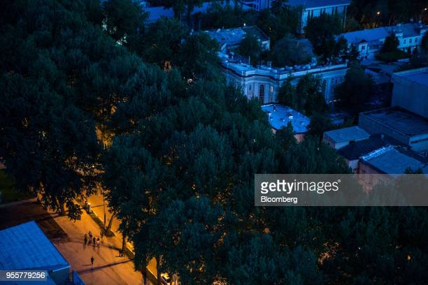 Pedestrians walk along a road as buildings stand illuminated at night in Dushanbe Tajikistan on Saturday April 21 2018 Flung into independence after...