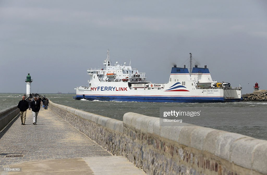 Pedestrians walk along a sea wall as the 'Nord Pas De Calais' roll-on, roll-off (RoRo) ferry, operated by MyFerryLink, a unit of Groupe Eurotunnel SA, leaves the Port of Calais in Calais, France, on Thursday, July 11, 2013. Eurotunnel was barred by the U.K. Competition Commission from operating a ferry service between France and Dover in the U.K. on concern it would give it too much dominance on the Channel traffic route. Photographer: Chris Ratcliffe/Bloomberg via Getty Images