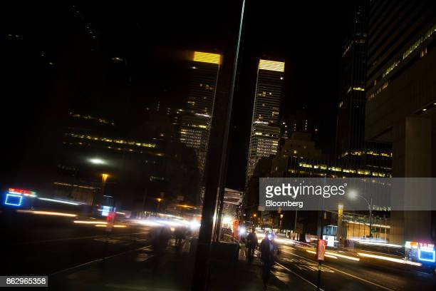 Pedestrians walk along a sidewalk as 731 Lexington Avenue stands lit in orange in the background to support a bid for Amazoncom Inc's second...