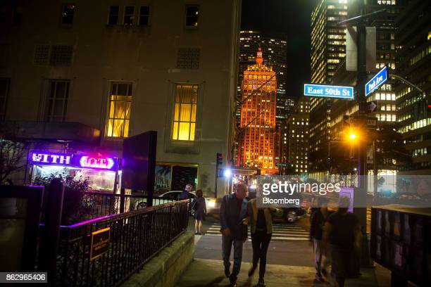 Pedestrians walk along a sidewalk as The Helmsley Building stands lit in orange to support a bid for Amazoncom Inc's second headquarters in New York...
