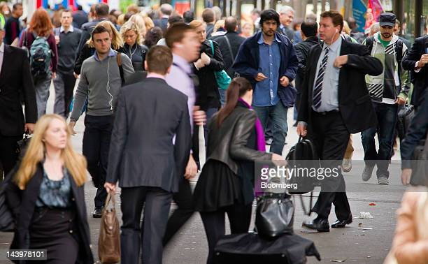 Pedestrians walk along a sidewalk during the morning rush hour in Sydney Australia on Monday May 7 2012 The Australian government intends to deliver...