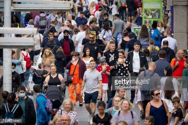 Pedestrians walk along a street in central London on July 26, 2021. - For the first time in the latest wave of coronavirus covid-19 infections, the...