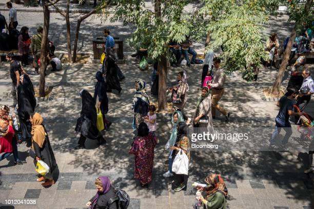 Pedestrians walk along a street in central Tehran Iran on Monday Aug 6 2018 Irans central bank acting on the eve of US sanctions scrapped most...