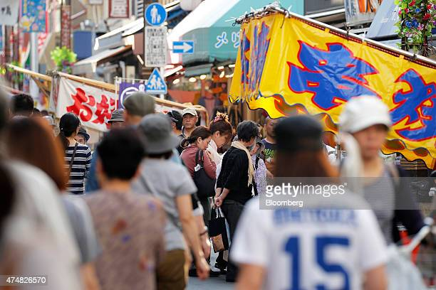 Pedestrians walk along a street in the Sugamo district of Tokyo Japan on Sunday May 24 2015 Japan's Topix index fell for the first time in nine days...