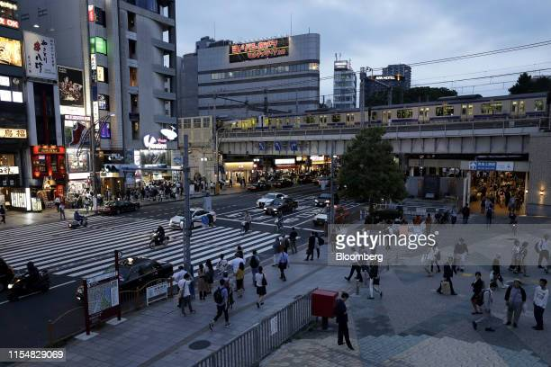 Pedestrians walk along a street while a train travels on an elevated railway track at dusk in Tokyo, Japan, on Tuesday, July 9, 2019. Japans wages...