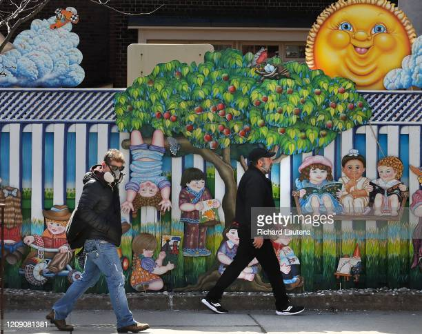 Pedestrians walk along Bloor Street in the sunshine past a closed child care centre near Ossington. The city continues under the threat of the...
