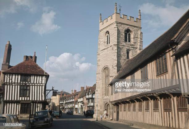 Pedestrians walk along Chapel Street, with the Grammar School of King Edward VI building on right and Guild Chapel behind, in Stratford-upon-Avon,...