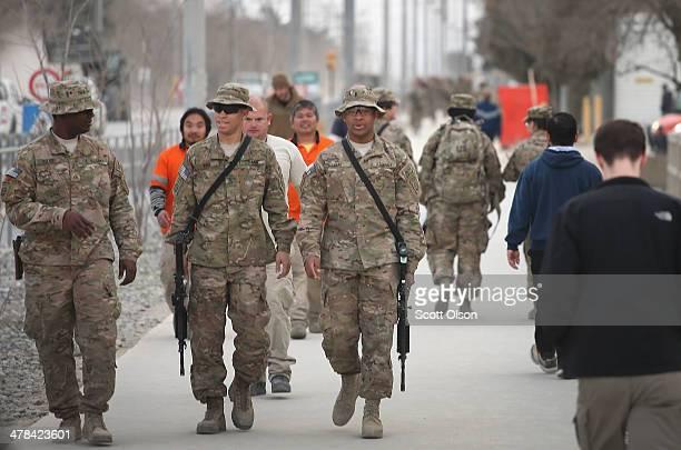 Pedestrians walk along Disney Street at Bagram Airfield on March 13 2014 near Bagram Afghanistan The street is the main street that runs through the...