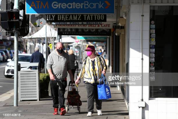 Pedestrians walk along High Street wearing face masks in Penrith on August 09, 2021 in Sydney, Australia. Restrictions for the suburbs of Penrith...