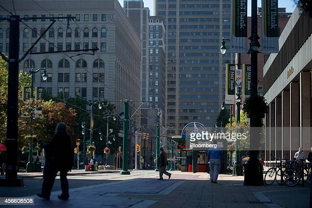Pedestrians walk along Main Street in Buffalo, New York, U.S., on Wednesday, Sept. 24, 2014. The Federal Reserve Bank of New York's empire state...