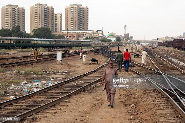 Pedestrians walk along rail tracks as a train and residential buildings stand in the background in Karachi Pakistan on Friday May 29 2015 Pakistan's...