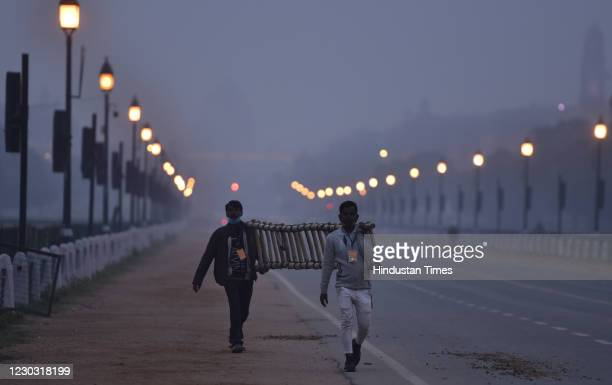 Pedestrians walk along Rajpath as Rashtrapati Bhawan is seen in the background engulfed in dense smog, on December 27, 2020 in New Delhi, India. Cold...