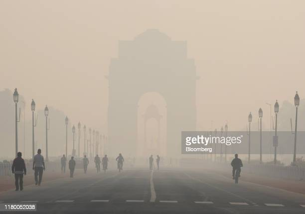 Pedestrians walk along Rajpath boulevard as India Gate monument stands shrouded in smog in New Delhi, India, on Tuesday, Nov. 5, 2019. Air pollution...