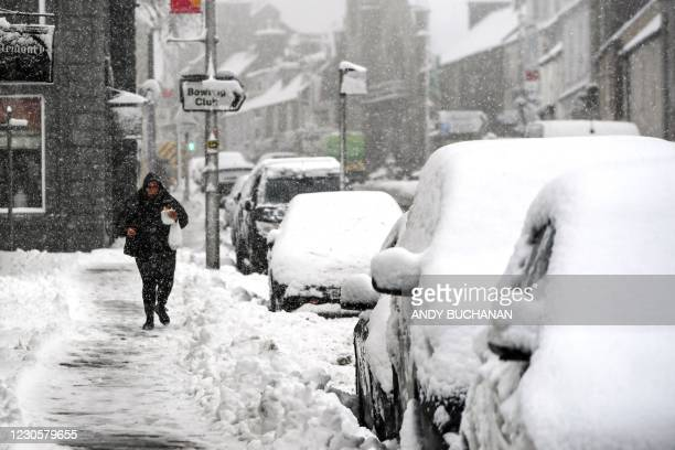Pedestrians walk along snow covered pavements in Auchterarder as heavy snow fell on parts of Scotland on January 14, 2021.